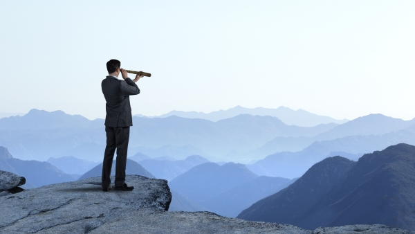 man in a suit standing on a cliff looking into a telescope