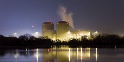 far off shot of a nuclear power plant at night